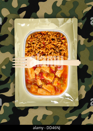 Military food rations or MRE Meals Ready to Eat on a camouflaged background. Packages open with plastic utensils. - Stock Photo