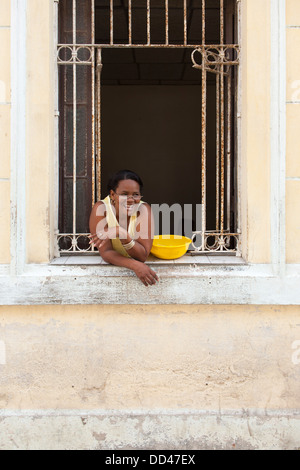 A Cuban Lady smiles and laughs while leaning out from a window in Havana, capitol city of Cuba - Stock Photo