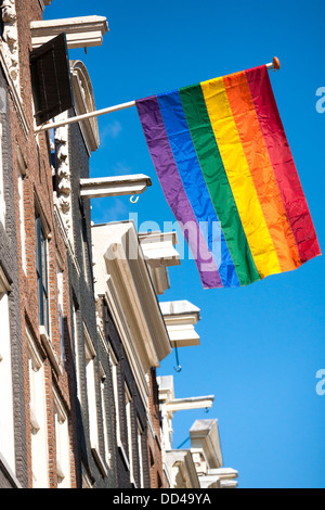 Rainbow colored flag flies from a typical row of canal houses in Amsterdam during Gay Pride, LGBT emancipation event. - Stock Photo
