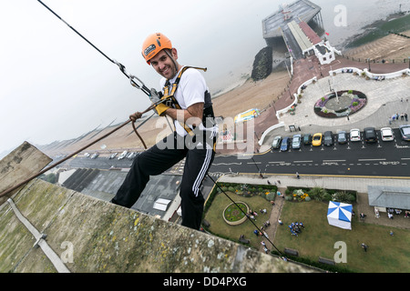 People Abseiling from a tower block for charity - Stock Photo