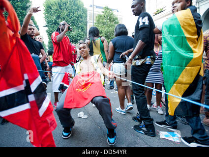 London, UK - 26 August 2013:  a young man dances during the annual parade at the Notting Hill Carnival. - Stock Photo