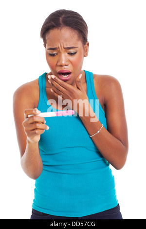 portrait of shocked African woman looking at pregnancy test - Stock Photo