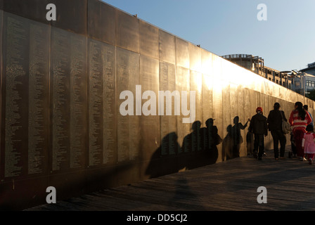 A family group walking beside the Welcome Wall at Darling Harbour, Sydney, Australia, in the late afternoon sun, - Stock Photo