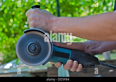 Switched on angle grinder in the man hands. Closeup. - Stock Photo