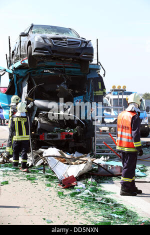 Rescue workers stand on the A9 Autobahn after a serious traffic accident near Eisenberg, Germany, 27 August 2013. - Stock Photo