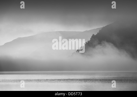 The rising sun created gaps in the fog bank hanging over Ullswater and in doing so gave glimpses of the opposite - Stock Photo