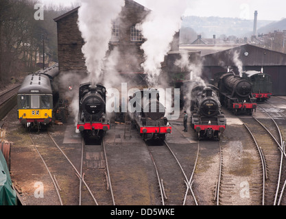 a row of steam locomotives and a classic 1960s diesel engine warming up prior to a gala day in Haworth - Stock Photo