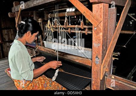 young woman weaving silk on loom Inle Lake Myanmar - Stock Photo