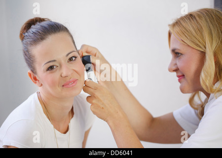 ENT physician Examining the Ear from Female Patient - Stock Photo
