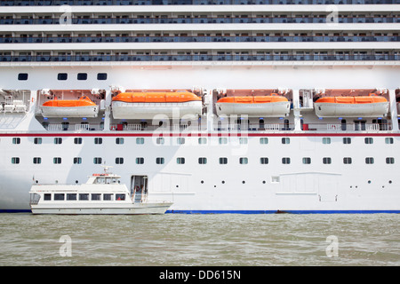 small boat and large cruise ship in the harbor of venice - Stock Photo