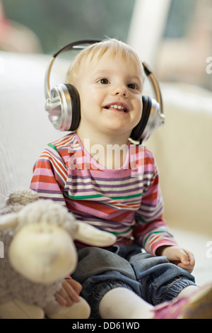 Toddler boy listens to music wearing headphones, Osijek, Croatia, Europe - Stock Photo