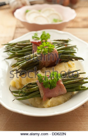 Plate of beans with raw ham and mashed potatoes on wooden table, close up - Stock Photo