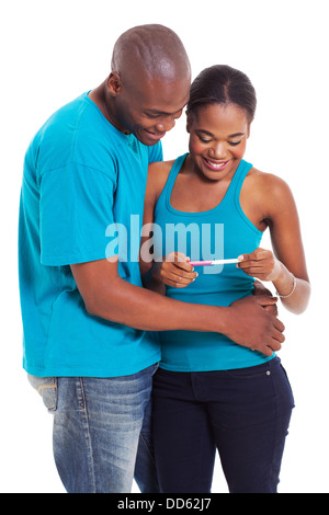 happy African couple looking at home pregnancy test on white background - Stock Photo