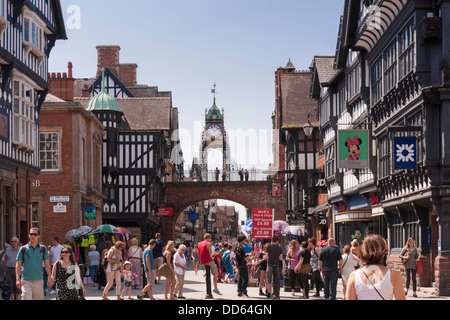 A busy shopping afternoon on a warm Summer's day in the Roman City of Chester, looking up Eastgate toward the Eastgate - Stock Photo