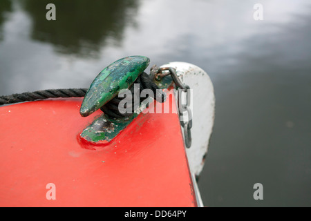 The bow of a Narrow boat's (barge) Iron fixing point, the boat is painted in bright red and green. The paint is - Stock Photo