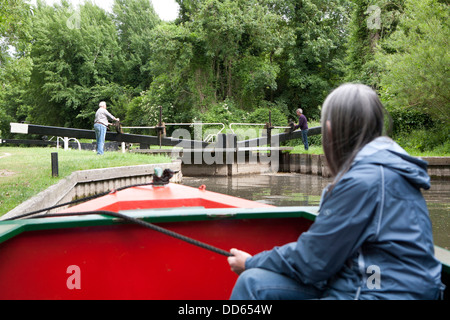 A close view ofwoman holding a rope securing a narrow boat (Barge) whilst a Lock is opened in the distance. - Stock Photo