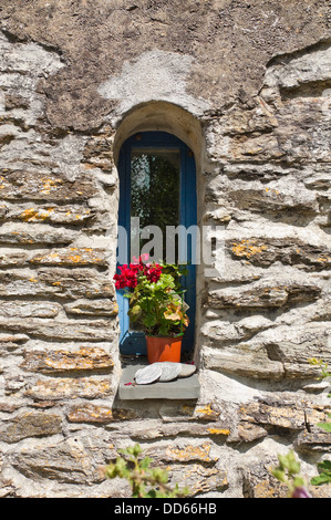 Vertical close up of a small arched window in an old stone cottage. - Stock Photo