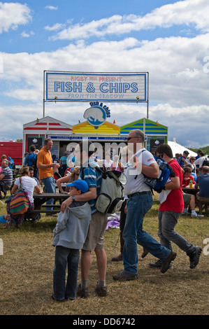 Vertical view of people standing by a fish and chip stall at a festival in the sunshine. - Stock Photo