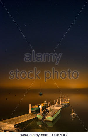 Germany, View of wooden jetty with boat in lake constance - Stock Photo