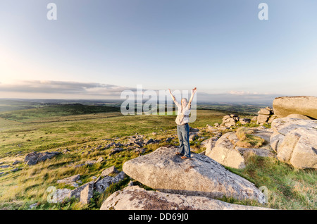 Woman standing with arms outstretched on on top of Kilmar Tor on Bodmin Moor in Cornwall, vintage effect. - Stock Photo