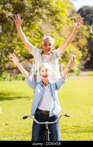 happy playful senior couple having fun riding bicycle outdoors - Stock Photo