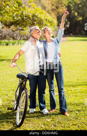 happy middle aged couple walking in park - Stock Photo