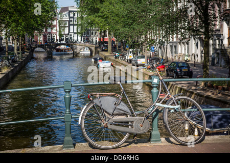 Bicycle on a bridge over an Amsterdam canal - Stock Photo