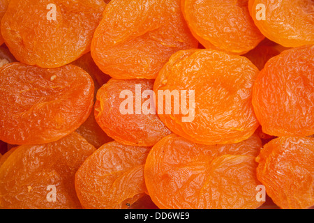 A close up of bright orange dried apricots fill the frame - Stock Photo