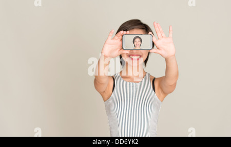 Young woman smile and take a picture of herself with the camera in a mobile phone - Stock Photo