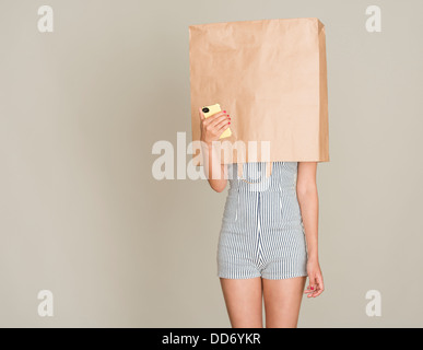 Anonymous caller. Young woman with paper bag over her head holding a mobile phone. - Stock Photo