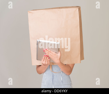 Anonymous internet surfing. Young woman with paper bag over her head holding a tablet - Stock Photo