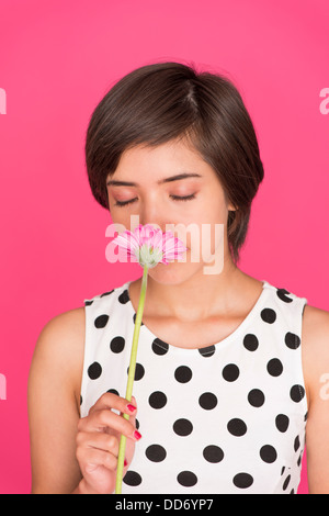 Romantic portrait of young multiracial woman smelling a gerbera daisy with closed eyes - Stock Photo