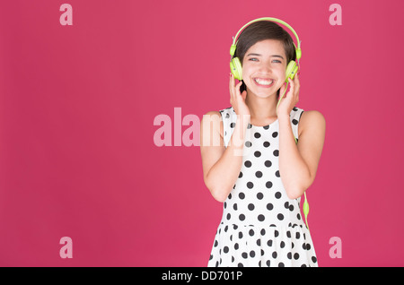 Beautiful young multiracial woman laughing and listening to music with green headphones - Stock Photo