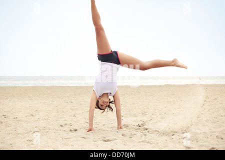 Happy outdoor female doing cartwheel on the beach. Healthy and active lifestyle shot expressing happiness and joy. - Stock Photo