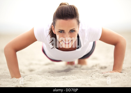 Happy fitness caucasian woman on the beach smiling while doing push up exercise. Active and healthy lifestyle. - Stock Photo
