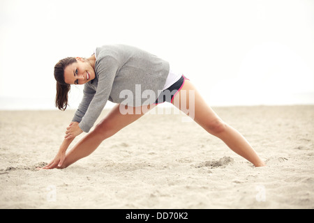 Young smiling female doing her stretching exercises on the sand as a part of a healthy and happy lifestyle. - Stock Photo