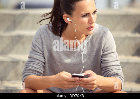 Young female athlete resting and listening to mp3 music outdoors - Stock Photo
