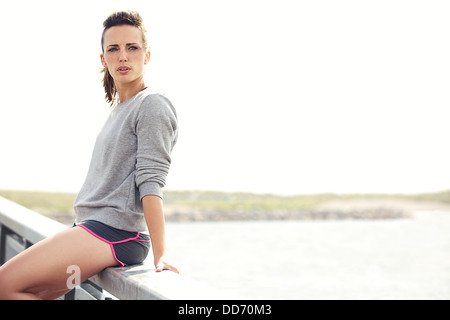Tired woman sitting and resting after running workout in nature - Stock Photo