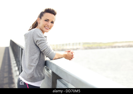 Happy smiling woman in fitness wear resting after running workout. Looking relaxed at camera. Copy space right. - Stock Photo