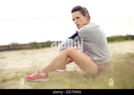 European woman resting and sitting on the grass after running workout / exercise. - Stock Photo