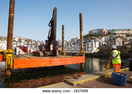 Surveyor positions a working pontoon off the quayside, Brixham Harbour, Devon, UK. - Stock Photo