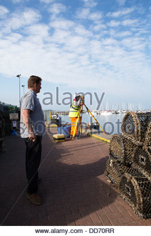 Surveyor works on the quayside while a man looks on, Brixham Harbour, Devon, UK - Stock Photo