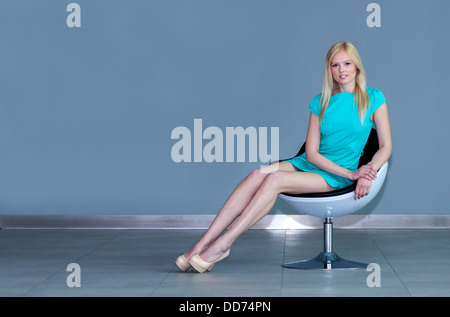 very attractive young blonde girl / woman in a emerald dress sitting on a white chair with her legs aligned - Stock Photo
