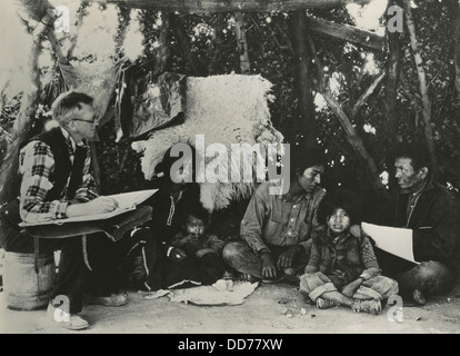 1940 Census taker, seated on a barrel, interviewing a Navajo family. At right is an Indian interpreter to assist - Stock Photo