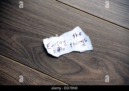 Enjoy the little things written on piece of paper, on a wood background. - Stock Photo