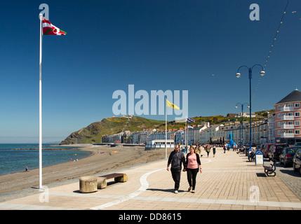 UK, Wales, Ceredigion, Aberystwyth, visitors walking on sunny promenade - Stock Photo