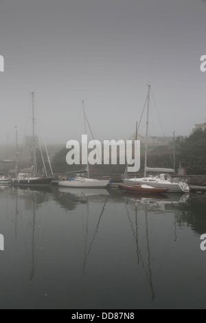 Sailing boats moored up in misty harbor - Stock Photo