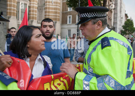 London, UK. 28th Aug, 2013. A policeman speaks to Turkish anti-war activists as they arrive to support a protest - Stock Photo