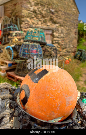 Lobster and crab pots stored above the harbour wall at Inner Hope Cove in the 'South Devon Area of Outstanding Natural - Stock Photo