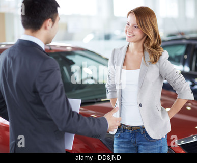 Successful young lady discussing her potential purchase with a car dealer - Stock Photo